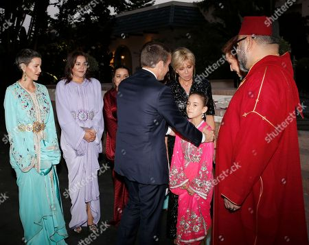 In this photo dated, French President Emmanuel Macron, center right, and his wife Brigitte Macron, 3rd right, are welcomed by the daughter of King Mohammed VI, Princess Lalla Khadija, as Morocco's King Mohammed VI, right, and his wife Princess Lalla Salma, 2nd right, look, before attending an Iftar meal, the evening meal when Muslims end their daily Ramadan fast at sunset, at the King Palace in Rabat, Morocco. The visit is the first by the recently elected French president to a North African country and aims to strengthen the relationship between France and Morocco, including cooperation on security issues