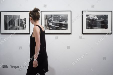 Stock Photo of A visitor looks at images during a press preview of the exhibition showcasing the photos taken by American photographer Elliott Erwitt during his visit to Hungary in 1964 in Mai Mano House of Hungarian Photographers in Budapest, Hungary, 15 June 2017.