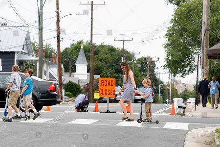 A woman and children cross the intersection of Mt. Vernon Ave. at E. Monroe Ave. in Alexandria, Va., that is blocked from traffic as FBI agents continue to investigate the scene the day after House Majority Whip Steve Scalise of La. was shot during during a congressional baseball practice