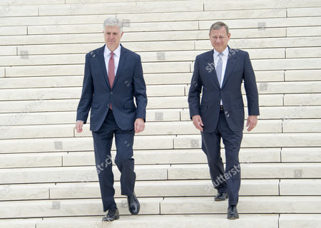 Chief Justice of the United States John G Roberts Jnr, Jr. and Associate Justice Neil M. Gorsuch walk down the front steps of the US Supreme Court Building as they pose for photos after the investiture ceremony for Justice Gorsuch in Washington, DC.
