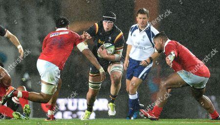 Seb Davies of Wales takes on Valentino Mapapalangi of Tonga.