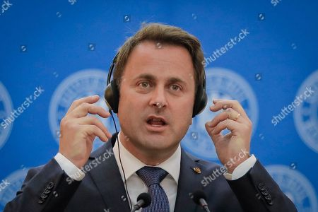 Luxembourg Premier Xavier Bettel reaches for his headphones during joint statements with Romanian counterpart Sorin Grindeanu in Bucharest, Romania, . The prime minister of Luxembourg has urged Romania to speedily resolve a political crisis sparked when the ruling party withdrew support for the prime minister who then refused to step down