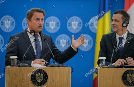 Luxembourg Premier Xavier Bettel, left, gestures during joint statements with Romanian counterpart Sorin Grindeanu in Bucharest, Romania, . The prime minister of Luxembourg has urged Romania to speedily resolve a political crisis sparked when the ruling party withdrew support for the prime minister who then refused to step down