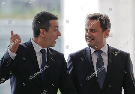 Luxembourg Premier Xavier Bettel, right, looks at Romanian counterpart Sorin Grindeanu, during a welcoming ceremony in Bucharest, Romania, . The prime minister of Luxembourg has urged Romania to speedily resolve a political crisis sparked when the ruling party withdrew support for the prime minister who then refused to step down
