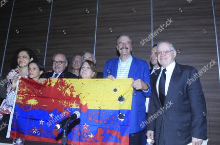 Stock Photo of Mexican Senator Mariana Gomez del Campo; Oriette Capriles; Executive Director of IDEA Asdrubal Aguiar; former president of Colombia Andres Pastrana; Mitzy Capriles of Ledezma; former president of Mexico Vicente Fox Quesada; former president of Bolivia Jorge Tuto; and former president of Costa Rica Miguel Anguel Rodriguez pose with a Venezuelan flag depicting blood stains and bullet holes during a meeting on the situation of Venezuela in Mexico City, Mexico, 16 June 2017. A total of 23 Ibero-American former presidents signed the so-called Declaration of Mexico, denouncing the situation in Venezuela and calling for the suspension of the Constituent Assembly proposed by the Government of Nicolas Maduro, considering that it represents an 'end' to democracy. The document, presented today in Mexico City, is a call to action to the participants of the meeting of foreign ministers on Venezuela, to be held on June 19 in Cancun, Mexico, before the formal inauguration of the General Assembly of the Organization of the American States (OAS).