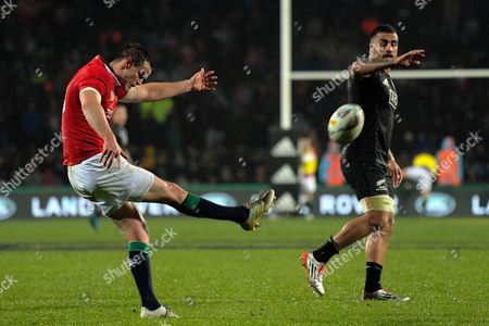 Jonny Sexton of the Lions puts up a kick watched by Liam Messam of the Maori