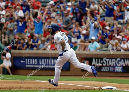 Fans stand and cheer as Texas Rangers' Mike Napoli rounds first watching his two-run home run that came off a pitch fromSeattle Mariners starting pitcher Yovani Gallardo in the first inning of a baseball game, in Arlington, Texas. The shot scored Carlos Gomez