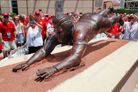 Fans gather around the newly dedicated statue of former Cincinnati Reds player Pete Rose outside Great American Ballpark prior to a baseball game between the Cincinnati Reds and the Los Angeles Dodgers, in Cincinnati