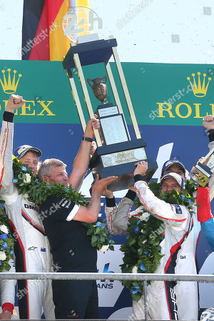 Driver Brendon Hartley of New Zealand, Fritz Enzinger, president of Porsche Team, Earl Bamber of New Zealand and German driver Timo Bernhard hold the Trophy during the podium ceremony of the 85th 24-hour Le Mans endurance race, in Le Mans, western France