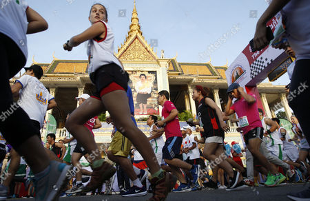Cambodians and foreigners run past a portrait of Queen Mother Norodom Monineath as they participate in the International Half Marathon in front of the Royal Palace in Phnom Penh, Cambodia, 18 June 2017. The Cambodian National Olympic Committee organizes the Phnom Penh International Half Marathon to celebrate Queen Mother Norodom Monineath's birthday.