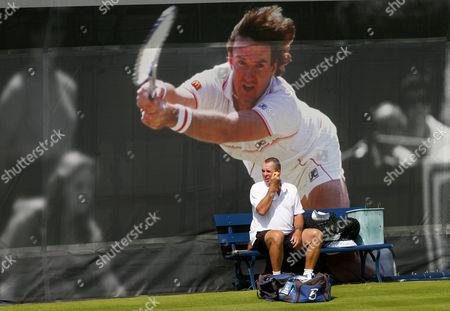 Ivan Lendl applies sun cream in front of a large Jimmy Connors poster