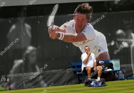 Stock Picture of Ivan Lendl, coach of Andy Murray, sits under a large poster of Jimmy Connors applying sun cream