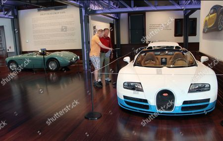 """Evan Hume Jr., left, of Washington, and Evan Hume Sr., of Tallahassee, Fla., look at a one-of-a-kind white and blue 2013 Bugatti Veyron 16.4L Grand Sport Vitesse """"Le Ciel Californien"""" in the Audrain Automobile Museum in Newport, R.I. A 1954 Austin-Healey 100/4 BN1 Le Mans is displayed behind them"""