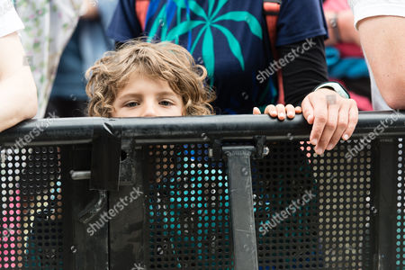 A young festival goer peers over the barrier at the front of the Pyramid Stage shortly before the first performance of the day by Hacienda Classical - Graeme Park, Mike Pickering & Manchester Camerata Orchestra.