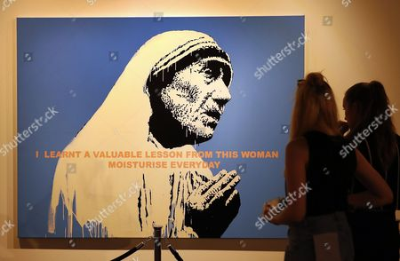 Two visitors look at the artwork entitled 'Mother Teresa' by British Banksy is on display at the exhibition 'The Art of Banksy' in Berlin, Germany, 20 June 2017. Original canvasses, paintings, sculptures and a interactive storytelling show the career of this unknown street artist. All pieces come from private collectors and the curator's Steve Lazarides collection. The exhibition runs from 15 June to 15 September 2017.