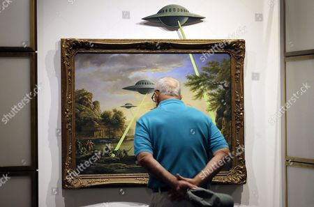 A visitor examines the painting entitled 'UFO' by British Banksy is on display at the exhibition 'The Art of Banksy' in Berlin, Germany, 20 June 2017. Original canvasses, paintings, sculptures and a interactive storytelling show the career of this unknown street artist. All pieces come from private collectors and the curator's Steve Lazarides collection. The exhibition runs from 15 June to 15 September 2017.