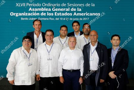 U.S. Deputy Secretary of State John Sullivan, center, poses for a group photo with Venezuelan opposition lawmakers and an opposition leader; Deputy Luis Florido, second left, front row; Deputy William Davila, second right; political coordinator of Voluntud Popular Carlos Vecchio, right; Deputy Carlos Lozano, left, back row; Deputy Franco Casella, second left, back row; Deputy Lester Toledo, third left, back row; Deputy Winston Flores, fourth left, back row, at the General Assembly of the Organization of American States in Cancun, Mexico, . Man on left, front row is unidentified