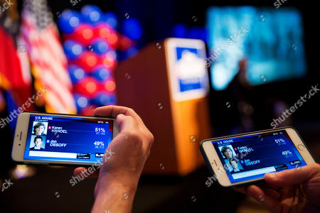 Supporters watch returns come in on their phones while attending the election night party of Democratic candidate for 6th congressional district Jon Ossoff in Atlanta