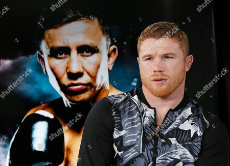 "Saul Canelo Alvarez Six-time boxing title holder Saul ""Canelo"" Alvarez, right, of Mexico sits beside a giant photograph of upcoming opponent, IBF and WBC world middleweight champion Gennady Golovkin during an interview, at The Associated Press headquarters in New York. In the most anticipated superfight since Mayweather- Pacquiao, the pair will face off Sept. 16th in Las Vegas. Referring to the bout, Alvarez said, ""It's gonna be a tough fight and (my team) is aware of this. But people wanted to see this fight and that's why we made it happen, to delight the fans"