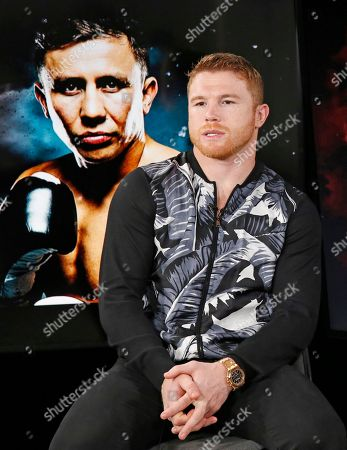 "Saul Canelo Alvarez Six-time boxing title holder Saul ""Canelo"" Alvarez, of Mexico, sits beside a giant photographic portrait of his upcoming opponent, IBF and WBC world middleweight champion Gennady Golovkin, during an interview, at The Associated Press headquarters in New York. In a highly anticipated boxing ""superfight,"" Alvarez will face Golovkin Sept. 16th in Las Vegas. Alvarez said, ""It's gonna be a tough fight and (my team) is aware of this. But people wanted to see this fight and that's why we made it happen, to delight the fans"