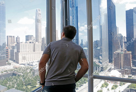 "WBC and IBF middleweight champion boxer Gennady Golovkin peers out of a window overlooking the Wolrd Trade Center complex following an interview at The Associated Press, in New York. Glolovkin is scheduled to fight eight-time title holder Saul ""Canelo"" Alvarez of Mexico in what is being billed as a boxing superfight"