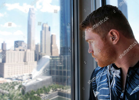 "Sal Canel Alvarez Eight-time boxing title holder Saul ""Canelo"" Alvarez of Mexico peers out of a window overlooking the World Trade Center complex following an interview at The Associated Press, in New York. Alvarez is scheduled to fight WBC and IBF middleweight champion Gennady Golovkin Sept. 16th in Las Vegas in what is being billed as boxing's biggest superfight since Mayweather-Pacquiao two years ago"