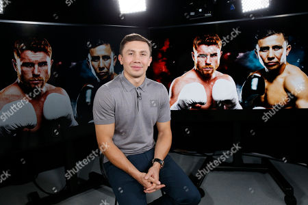 "IBF and WBC middleweight title holder Gennady Golovkin is shown with pictures of himself and his upcoming opponent Saul ""Canelo"" Alvarez. second from right, behind him, during an interview with The Associated Press, in New York"