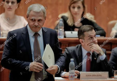 Head of the Ruling Social Democratic Party, Liviu Dragnea, left, prepares to deliver a speech as Prime Minister Sorin Grindeanu, right sits at the Romanian parliament in Bucharest, Romania, . Romania's Prime Minister Sorin Grindeanu and his government were ousted Wednesday in a no-confidence vote submitted by the ruling Social Democratic Party