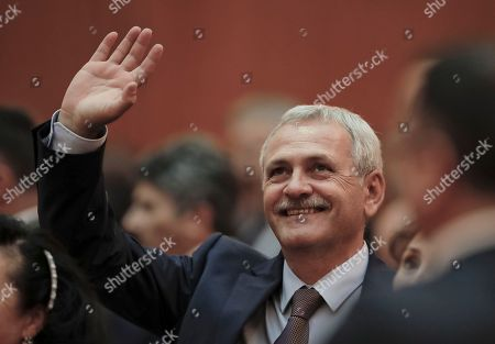 Head of the Ruling Social Democratic Party, Liviu Dragnea waves to supporters at the Romanian parliament in Bucharest, Romania, . Romania's Prime Minister Sorin Grindeanu and his government were ousted Wednesday in a no-confidence vote submitted by the ruling Social Democratic Party