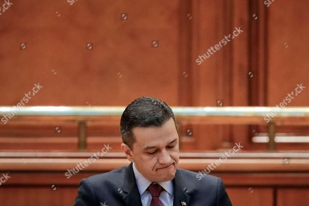 Prime Minister Sorin Grindeanu, grimaces during his speech before a no-confidence vote against his government at the Romanian parliament in Bucharest, Romania, . Romania's Prime Minister Sorin Grindeanu and his government were ousted Wednesday in a no-confidence vote submitted by the ruling Social Democratic Party