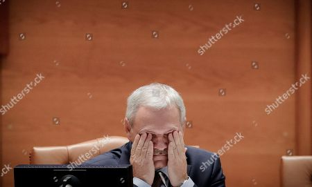Head of the Ruling Social Democratic Party, Liviu Dragnea wipes his eyes at the Romanian parliament in Bucharest, Romania, . Romania's Prime Minister Sorin Grindeanu and his government were ousted Wednesday in a no-confidence vote submitted by the ruling Social Democratic Party