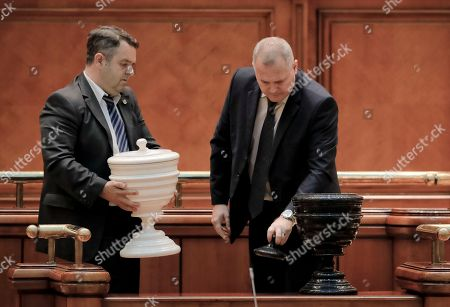 Two men set up voting urns before a no-confidence vote initiated by the ruling Social Democratic Party against its own government at the Romanian parliament in Bucharest, Romania, . Romania's Prime Minister Sorin Grindeanu and his government were ousted Wednesday in a no-confidence vote submitted by the ruling Social Democratic Party