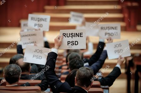"""Opposition lawmakers hold papers that read """"Shame PSD"""" and """"Down PSD"""" during a no-confidence vote initiate by the ruling Social Democratic Party against its own government at the Romanian parliament in Bucharest, Romania, . Romania's Prime Minister Sorin Grindeanu and his government were ousted Wednesday in a no-confidence vote submitted by the ruling Social Democratic Party. PSD is the local abbreviation for the Social Democratic Party"""
