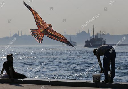 A man flies a kite while people enjoy their time off on the banks of the Bosphorus in Istanbul, Turkey, 21 June 2017. Seen on the opposite waterside are the Sultanahmet Mosque (L) and the Hagia Sophia Museum (R) in the Kadikoy district of Istanbul. The Turkish metropole on 21 June experienced pleasant weather with temperatures of 25 degrees Celsius on the longest day in the Northern Hemisphere.