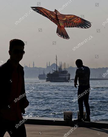 Stock Photo of A man flies a kite while people enjoy their time off on the banks of the Bosphorus in Istanbul, Turkey, 21 June 2017. Seen on the opposite waterside is the Hagia Sophia Museum (C) in the Kadikoy district of Istanbul. The Turkish metropole on 21 June experienced pleasant weather with temperatures of 25 degrees Celsius on the longest day in the Northern Hemisphere.