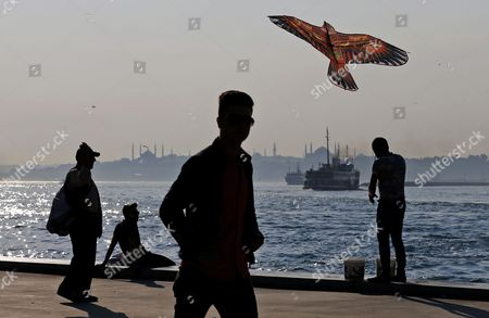 Stock Image of A man flies a kite while people enjoy their time off on the banks of the Bosphorus in Istanbul, Turkey, 21 June 2017. Seen on the opposite waterside are the Sultanahmet Mosque (L) and the Hagia Sophia Museum (R) in the Kadikoy district of Istanbul. The Turkish metropole on 21 June experienced pleasant weather with temperatures of 25 degrees Celsius on the longest day in the Northern Hemisphere.