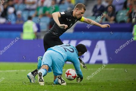 Mexico goalkeeper Alfredo Talavera grabs the ball ahead of New Zealand's Chris Wood during the Confederations Cup, Group A soccer match between Mexico and New Zealand, at the Fisht Stadium in Sochi, Russia