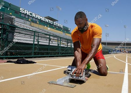 Sprinter Tyson Gay adjusts the starting block before taking a practice run, in Sacramento, Calif. Gay will be competing in the 100 and 200 meter races at the USA Track and Field Championships that starts Thursday and runs through Sunday