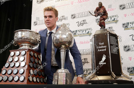 Connor McDavid of the Edmonton Oilers poses with the Art Ross Trophy, left, the Hart Memorial Trophy, center, and the Ted Lindsay Award after winning the honors during the NHL Awards, in Las Vegas