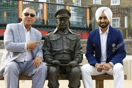 Stock Photo of Satinder Sartaaj sits with the statue of Dads Army character Captain Mainwaring and owner of Thetford's Thomas Paine Hotel Gez Chetal, left