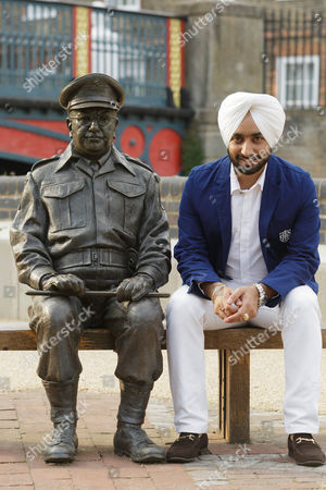 Stock Picture of Satinder Sartaaj sits with the statue of Dads Army character Captain Mainwaring