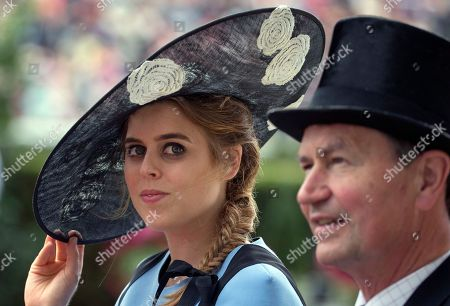Britain's Princess Beatrice, left, looks at the crowd as she arrives by open carriage with Timothy Laurence, husband of Princess Anne, on the third day of the Royal Ascot horse race meeting, which is traditionally known as Ladies Day, in Ascot, England