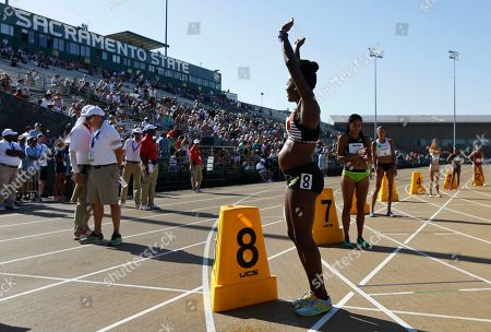 Alysia Montano, who is five months pregnant, waves to the crowd before a heat in the first round of the women's 800 meters at the U.S. Track and Field Championships, in Sacramento, Calif