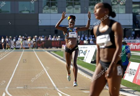 Alysia Montano, left, who is five months pregnant, crosses the finish line during the first round of the women's 800 meters at the U.S. Track and Field Championships, in Sacramento, Calif