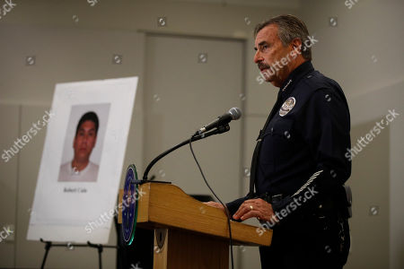 Los Angeles Police Chief Charlie Beck stands next to a display board showing an image of officer Robert Cain while speaking to reporters during a news conference, in Los Angeles. Cain has been arrested for allegedly having sex with a 15-year-old cadet who's suspected of joyriding in stolen patrol cars