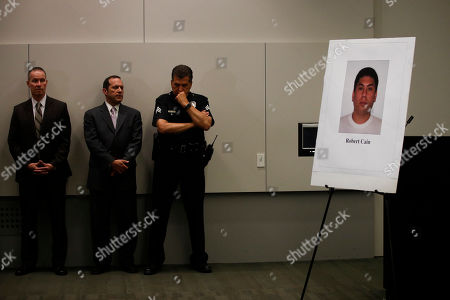 Stock Picture of Los Angeles police officials stand near a display board showing an image of officer Robert Cain as they listen to Police Chief Charlie Beck during a news conference, in Los Angeles. Cain has been arrested for allegedly having sex with a 15-year-old cadet who's suspected of joyriding in stolen patrol cars