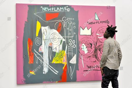 "Artist Bradley Theodore views ""New Flame"", 1985, a collaborative work by Andy Warhol and JEAN-MICHEL BASQUIAT (estimate GBP1.7-2.2m) at the preview of Sotheby's Contemporary Art Sale in New Bond Street."