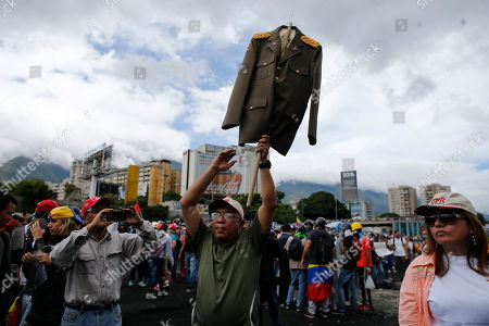 Retired Bolivarian National Guard Major Carlos Almeida raises his old military uniform on a stick as he protests against the government of President Nicolas Maduro, in Caracas, Venezuela, . Almeida who says that he has been retired for ten years commented that he is deeply disappointed with the current action of the Guard as demonstrators took to the streets asking restraint from security forces after more than 70 people have been killed during almost 90 days of protests seeking President Nicolas Maduro's removal