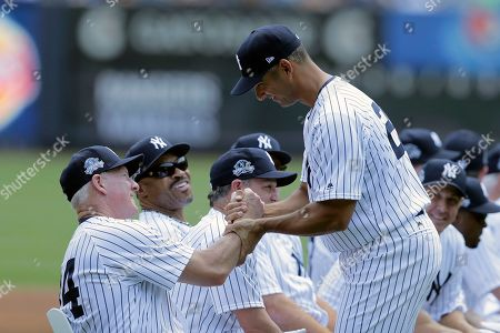 Former New York Yankee Jorge Posada, front right, shakes hands with other former players during Old-Timers' Day at Yankee Stadium, in New York