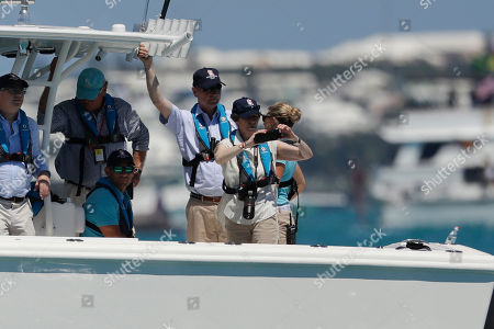 England's Princess Anne records with a phone as her husband Timothy Laurence, third from right, looks on after the eighth race of America's Cup sailing competition between Oracle Team USA and Emirates Team New Zealand, in Hamilton, Bermuda